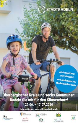 Ein Mann und ein Mädchen fahren Fahrrad. Sie tragen beide Fahrradhelme auf dem Kopf.