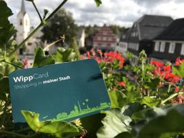 Die WippCard, im Hintergrund sind rote Blumen mit grünen Blättern und mehrere Gebäude am Marktplatz