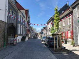 Das Bild zeigt die Marktstraße in Wipperfürth. Zwischen den Häusern sind weiß/rote Wimpelketten gespannt.