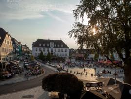 Marktplatz bei schönem Wetter und mit vielen Besucherinnen und Besuchern in den Biergärten