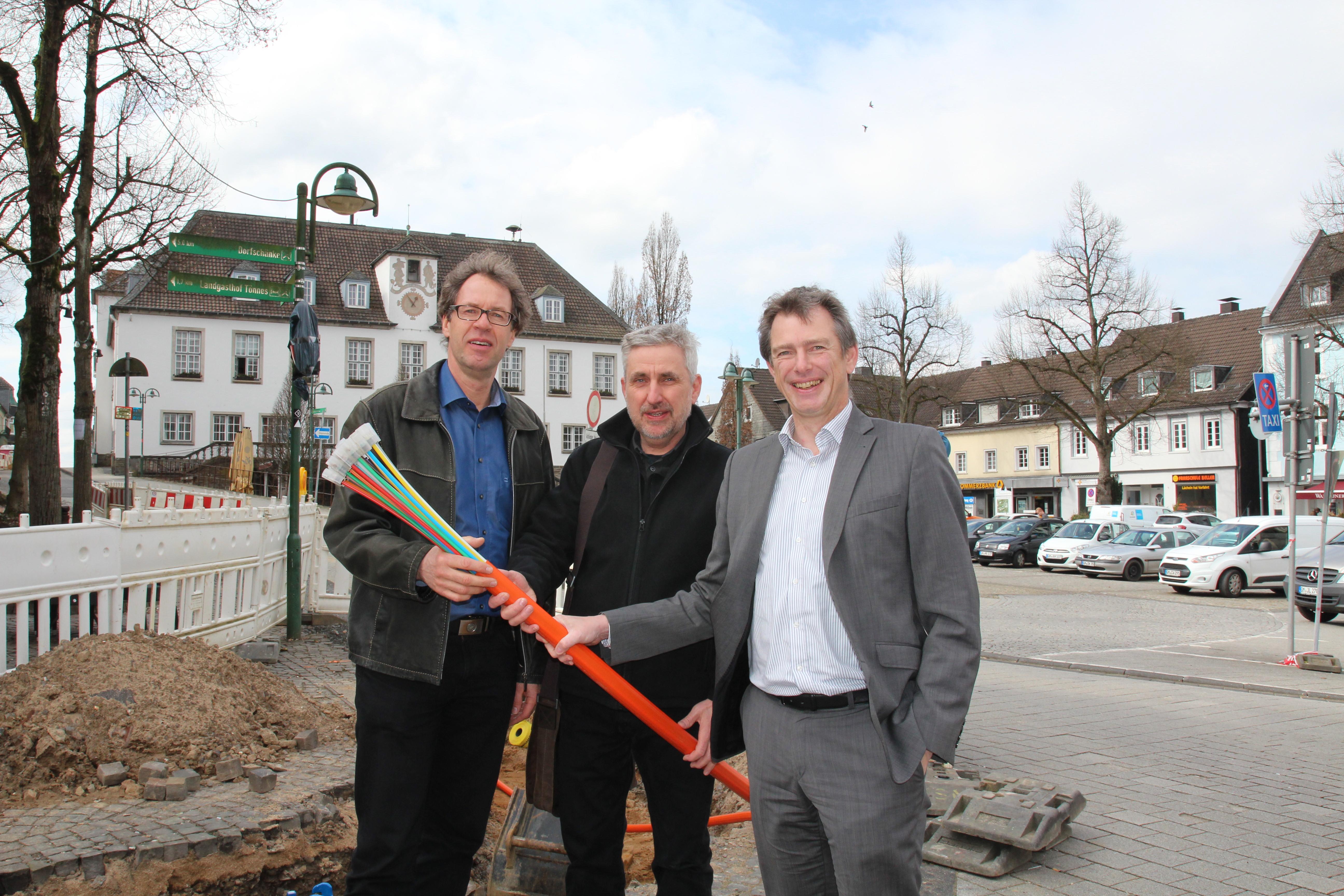Bürgermeister Michael v. Rekowski, städtischer Mitarbeiter Gerd Müller und Geschäftsführer Jens Langner von der BEW mit einem Leerrohr für den Breitbandausbau in der Hand